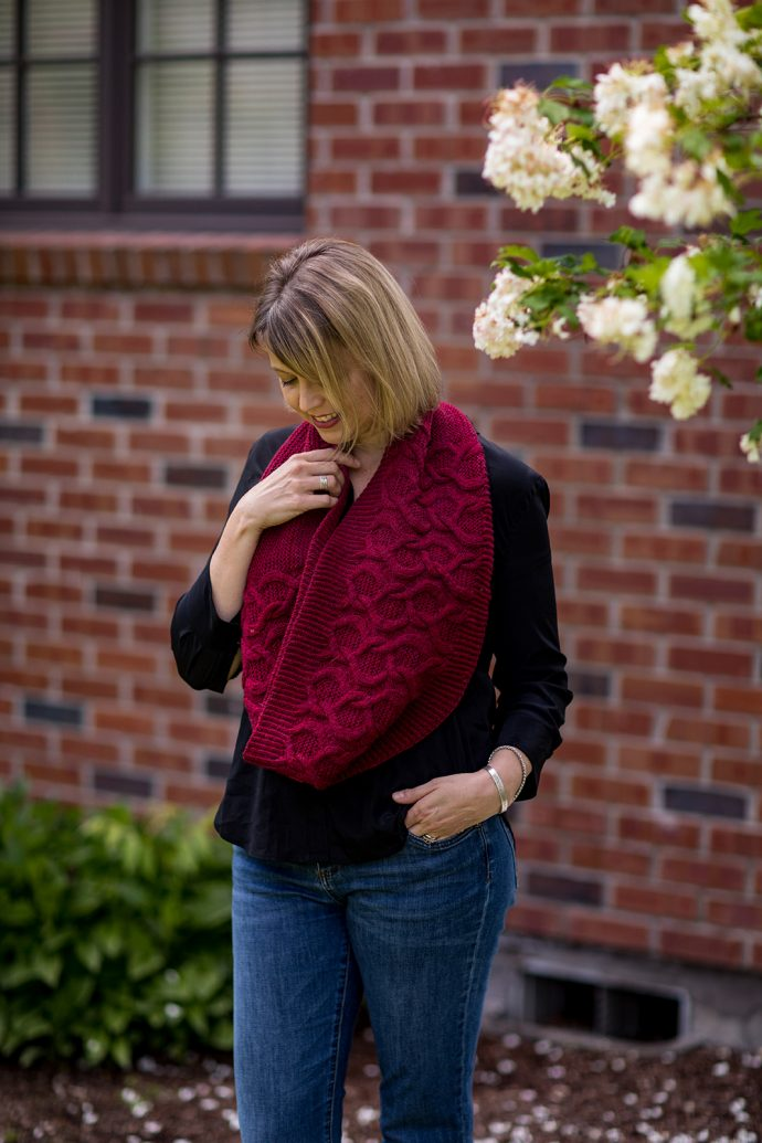 Woman wearing jeans, a black shirt and a hand knitted cowl
