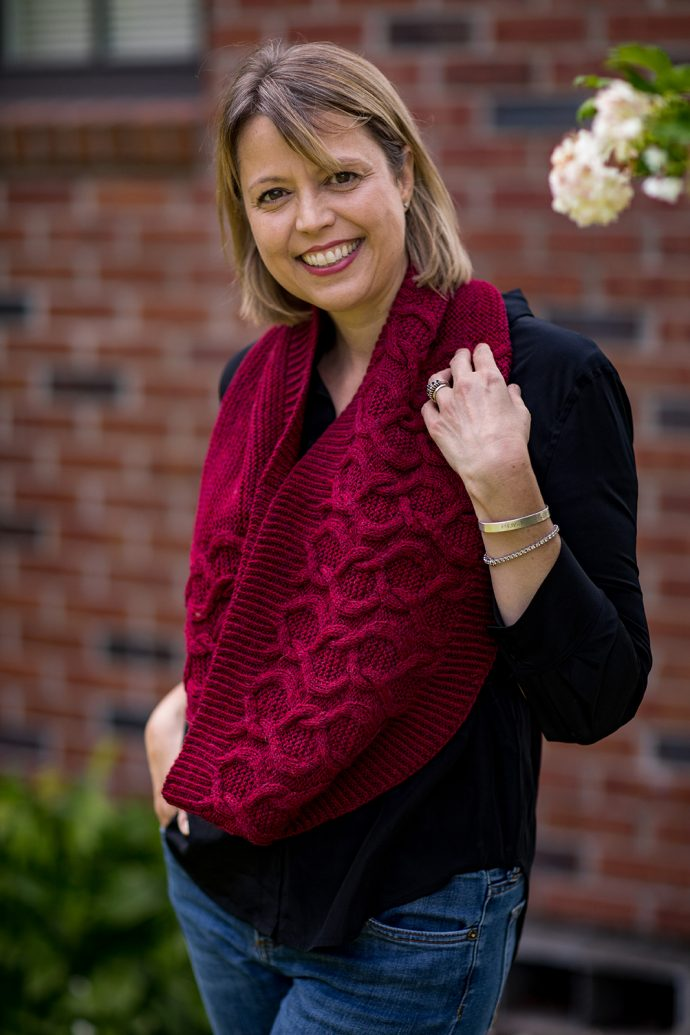 Smiling woman wearing jeans, a black shirt and a hand knitted cowl