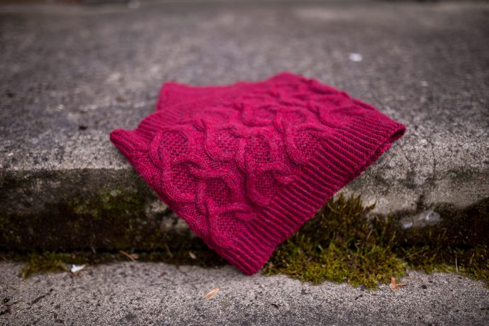 hand knitted cowl laying folded on a cement step
