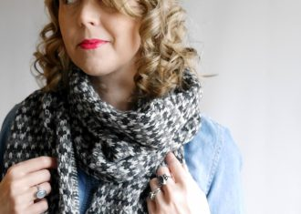 Woman with curly hair with red lips wearing hand knit scarf