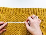 womans hands with measuring tape on a yellow garment