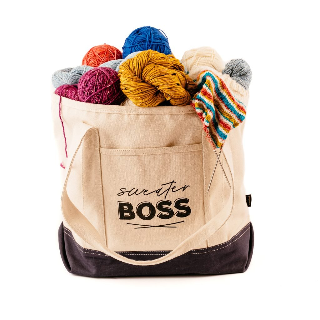 canvas tote bag filled with yarn and sweaters with the words sweater boss on the front