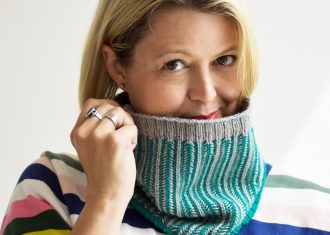 Woman with blonde hair wear a teal and grey handknit cowl that she is holding up to show the hand stitched detail so it covers her mouth