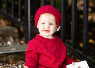 Smiling baby wearing bright red sweater and matching hat and holding a book