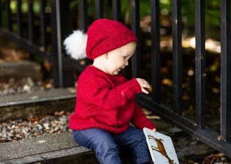 Side view of a toddler wearing bright red sweater and matching hat and holding a book