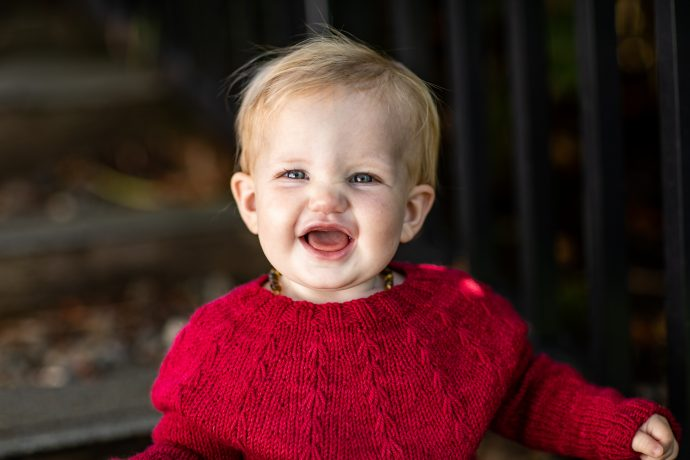 Laughing baby wearing bright red hand knit sweater