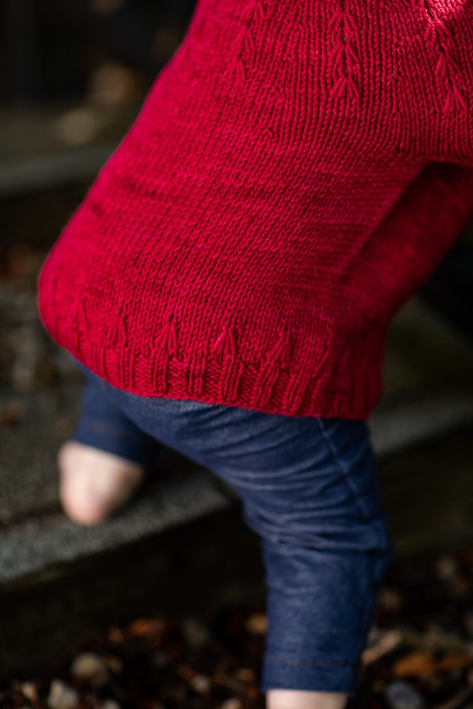 Detail of the Firecracker Pullover, a red sweater with firework-like details around the lower edge