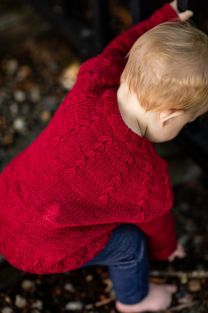 The back of a baby wearing a bright red hand knit sweater that features firework-like bursts around the yoke of the neck